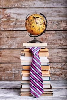 Pila di libri e cravatta. occhiali sul globo. la conoscenza è un viaggio.