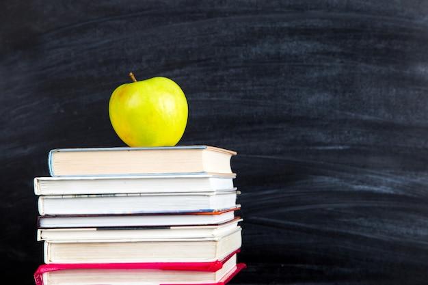 Una pila di libri, sulla cima di una mela, contro una lavagna nera, copia spazio.