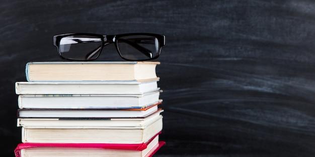 Una pila di libri, sopra gli occhiali, contro una lavagna nera, copia spazio.