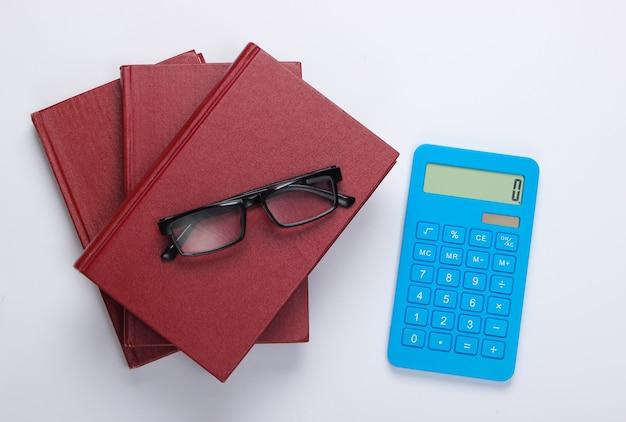 Pila di libri con la calcolatrice su bianco