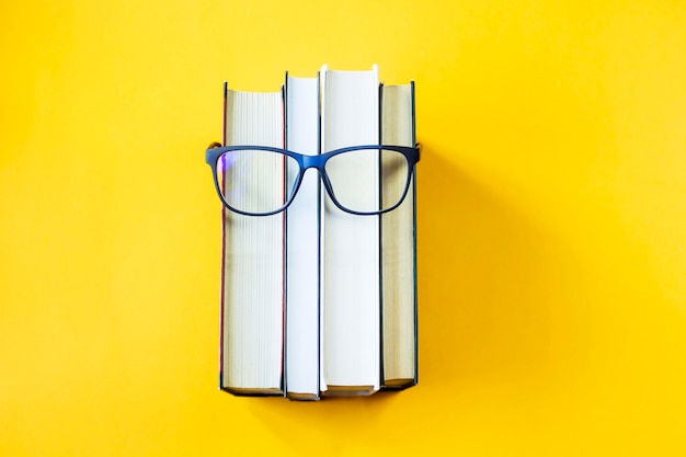 Una pila di libri con gli occhiali è un'immagine del volto di una persona