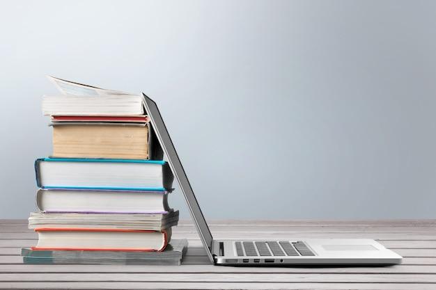 Pila di libri con laptop sul tavolo