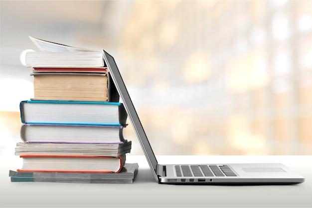Pila di libri con laptop