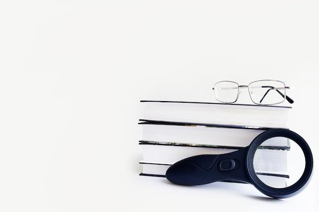 Una pila di libri con una lente d'ingrandimento e bicchieri su uno sfondo bianco, isolare.