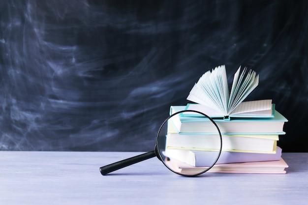 Pila di libri con lente d'ingrandimento sul tavolo e sfondo blu scuro