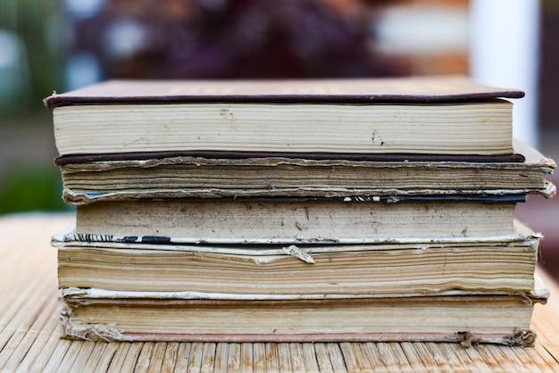 Pila di libri su una tavola di legno e bokeh verde