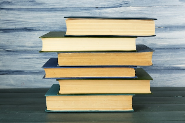Pila di libri sulla tavola di legno sulla parete di legno blu