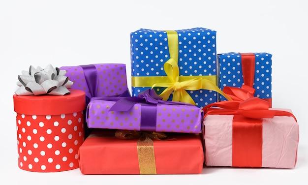 Pila di scatole avvolte in carta e legate con un nastro di seta su uno sfondo bianco, celebrazione. set di scatole regalo
