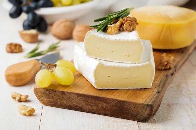 Impilare il formaggio camembert con uva, noci e basilico su una superficie di cemento grigio chiaro