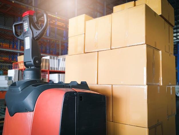 Pila di scatole di cartone e transpallet elevatore nel magazzino. spedizione e deposito merci.