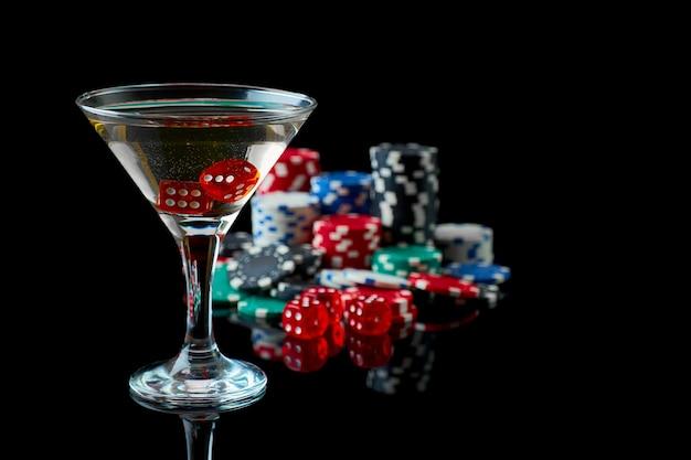 Pila di casino fiches bicchiere di martini vermouth e dadi rossi isolati su nero riflettente ...
