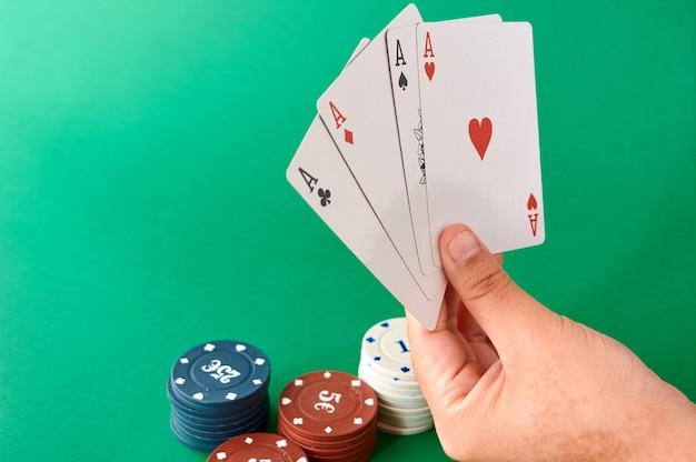 Pila di fiches e mano con quattro assi, panno da poker, un mazzo di carte, mano di poker e fiches. sfondo.