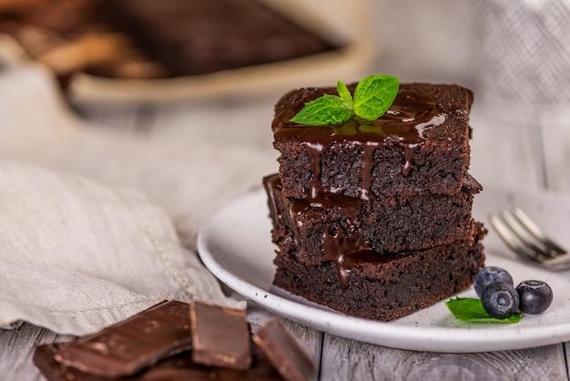Una pila di brownies al cioccolato su fondo di legno con foglia di menta in cima, prodotti da forno fatti in casa e dessert.
