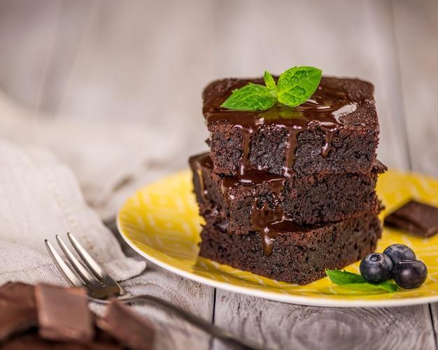 Una pila di brownie al cioccolato su una superficie di legno con foglia di menta in cima, prodotti da forno fatti in casa e dessert