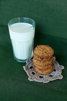 Pila di biscotti al cioccolato e bicchiere di latte.