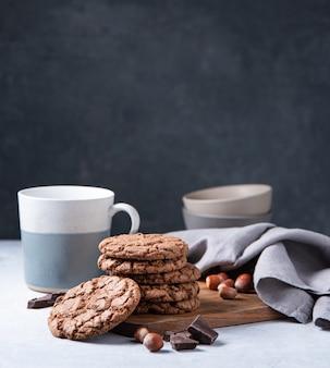 Una pila di biscotti al cioccolato con gocce di cioccolato e noci con una tazza di tè su un tavolo luminoso. vista frontale e copia spazio