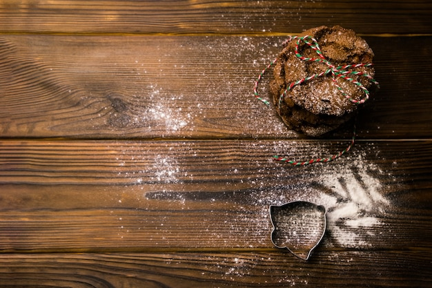 Pila di biscotti al cioccolato di natale legati con corda a strisce sulla tavola di legno testurizzata cosparsa di farina