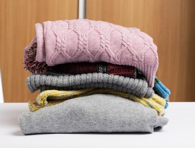 Pila di vestiti piegati puliti sul tavolo bianco, aiuto e concetto di volontariato. ordinamento delle cose