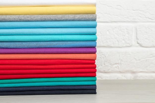 Una pila di vestiti colorati puliti, ordinatamente piegati su un tavolo di legno chiaro. colori dell'arcobaleno posto per il testo