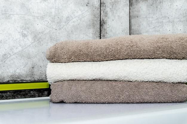 Una pila di asciugamani di cotone arrotolati puliti è di sfumature grigie sulla lavatrice in bagno.