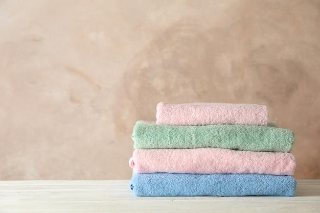 Pila di asciugamani puliti contro il marrone,