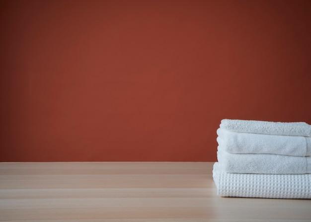 Pila di asciugamani puliti e accappatoio sul tavolo