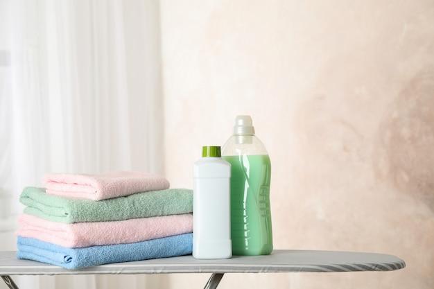Pila di asciugamani puliti e liquido per bucato sull'asse da stiro,