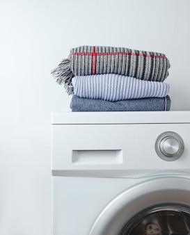 Pila di vestiti sulla lavatrice contro una superficie bianca
