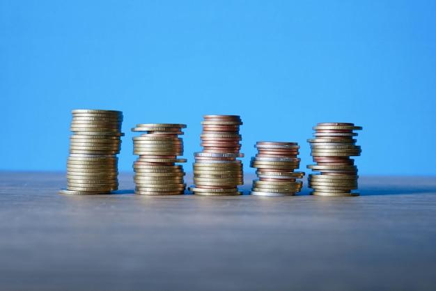 Pila monete concetto risparmiare denaro. monete su sfondo blu
