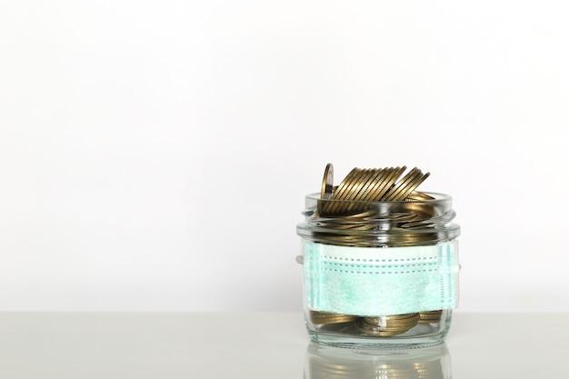La pila di soldi delle monete in bottiglia di vetro con l'uso della maschera medica protettiva su fondo bianco, risparmia i soldi per assicurazione medica e il concetto di sanità