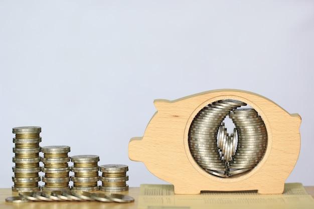 La pila di soldi delle monete in legno del porcellino salvadanaio su fondo bianco, i soldi di risparmio per prepara in futuro e il concetto di investimento