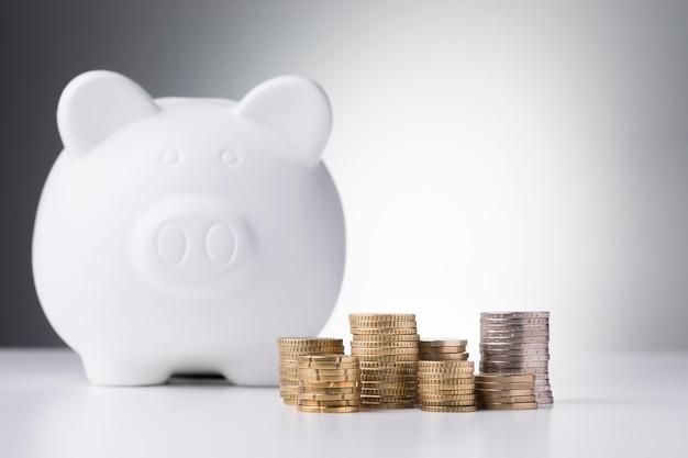 Pila di monete e salvadanaio