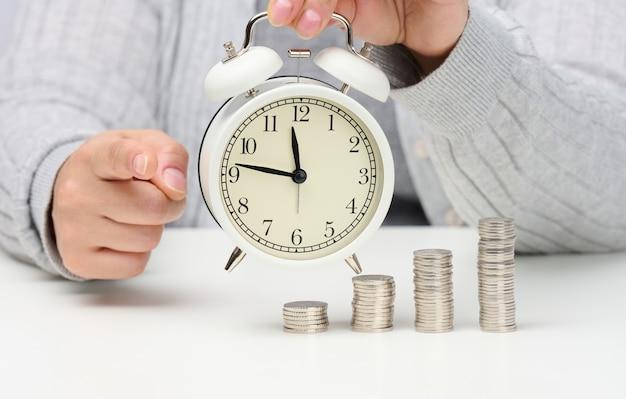 Pila di monete e sveglia bianca rotonda sul tavolo. il concetto di tempo è denaro, un periodo di sconti.