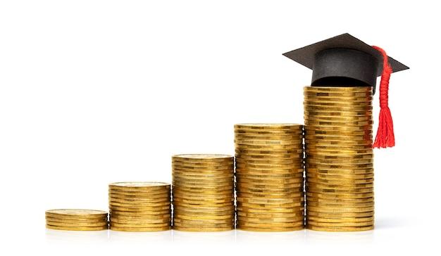 La pila di monete si alza e il cappello da laureato il concetto è un'istruzione costosa che investe in te stesso