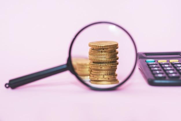 Pila di monete attraverso una lente di ingrandimento su uno sfondo rosa. monete in euro.