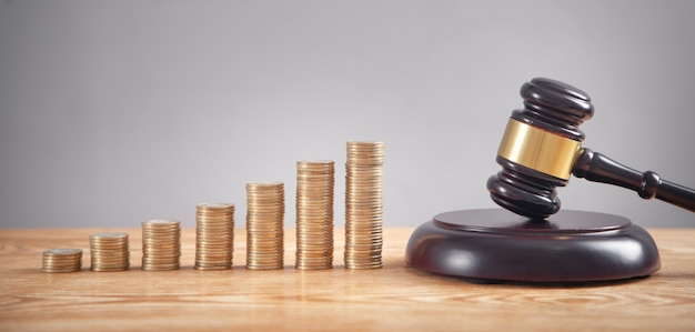 Pila di monete con il martelletto del giudice.