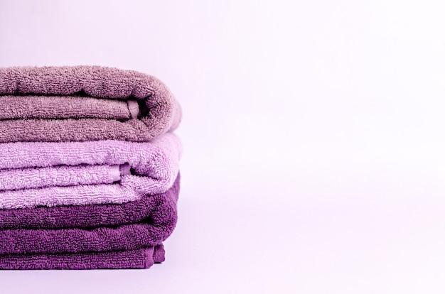 Pila di asciugamani da bagno colorati su sfondo bianco. igiene personale. copia spazio, posto per il testo. avvicinamento.