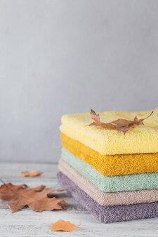 Pila di asciugamani da bagno colorati su sfondo chiaro. asciugamani in cotone dai colori pastello. igiene, tessuto, spa e concetto tessile textile