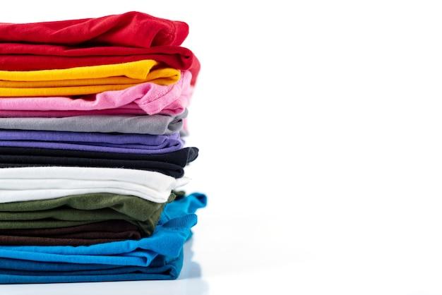 Pila di t-shirt in cotone colorato isolato su sfondo bianco.