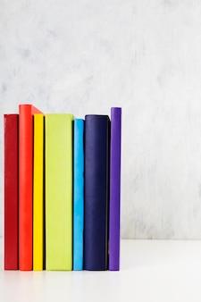 Pila di libri variopinti dell'arcobaleno su fondo bianco.