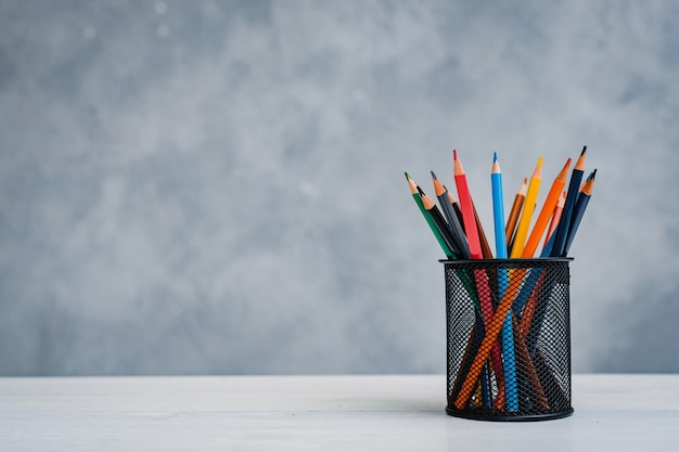 Una pila di libri di testo colorati e un bicchiere di matite luminose su un tavolo grigio-blu. concetto di istruzione, formazione, area di lavoro, spazio libero.