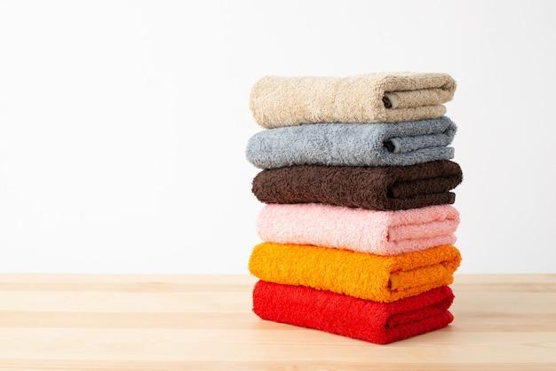 Pila di asciugamani colorati sulla tavola di legno