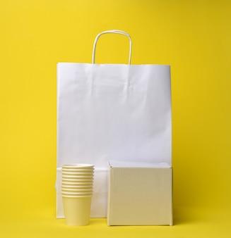 Pila di tazze, scatola e sacchetto usa e getta di carta bianca con manici su sfondo giallo, zero rifiuti