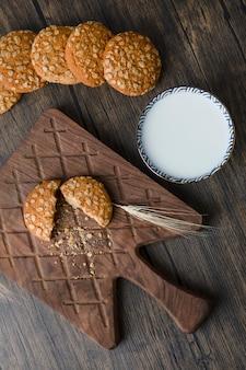 Pila di deliziosi biscotti con cereali e una ciotola di latte fresco.