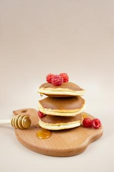 Una pila di deliziose frittelle fatte in casa con lamponi, versate con miele e un cucchiaio su un vassoio di legno.