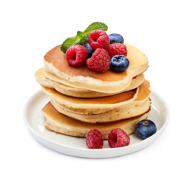 Pila di pancake deliziosi con le bacche e la foglia di menta sul piatto isolato su bianco.