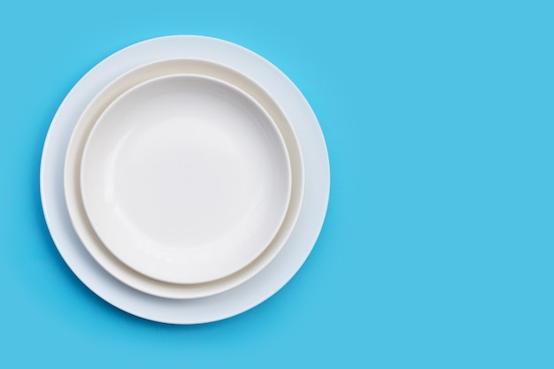 Pila di piatti su sfondo blu. copia spazio
