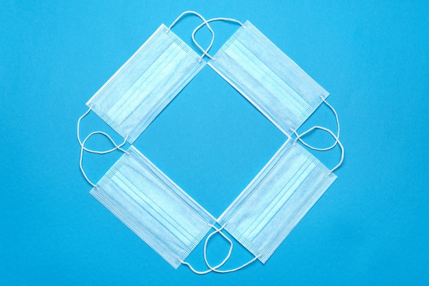 Pila di maschere viso mediche blu usa e getta su sfondo blu