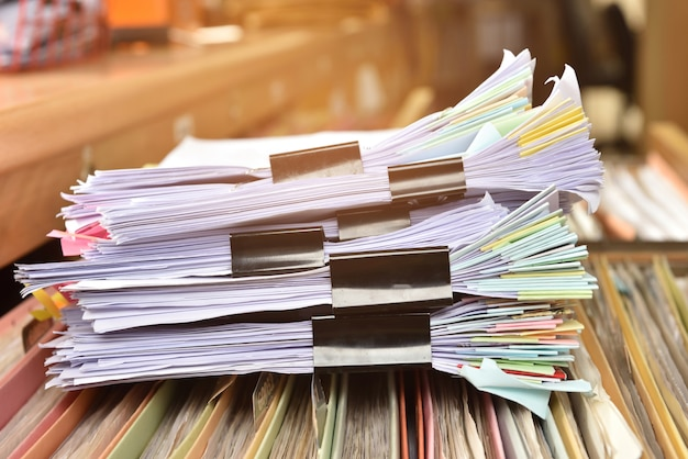 Impila il file del documento e il passo paperclip nero sul cabinet in ufficio.