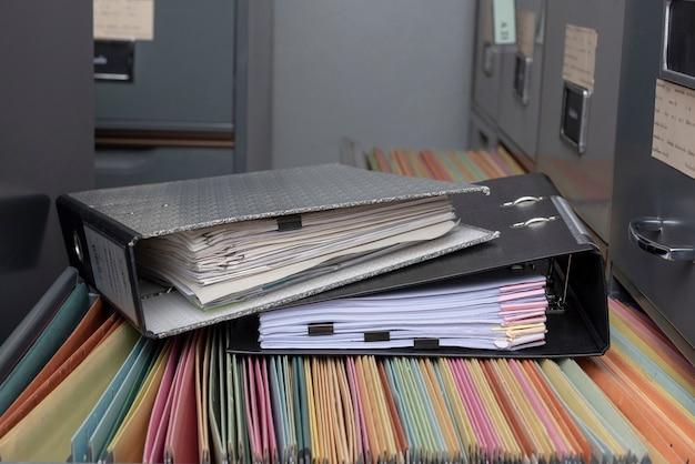 Stack file di file di documenti su cabinet in office.